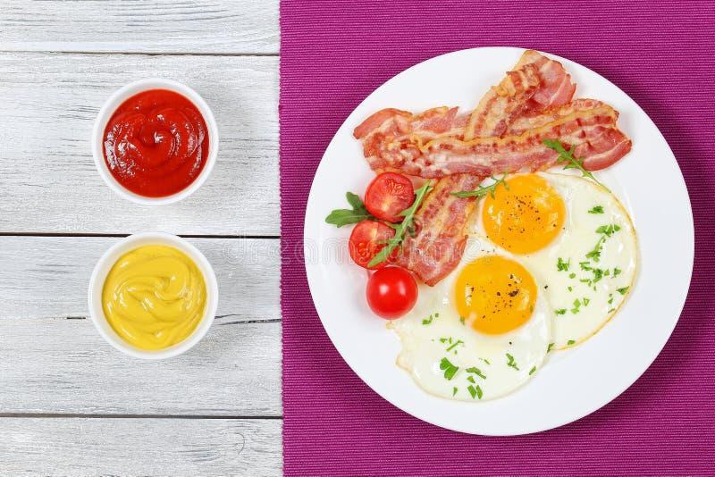 Knapperig gebraden bacon, Sunny Side Up Eggs stock fotografie
