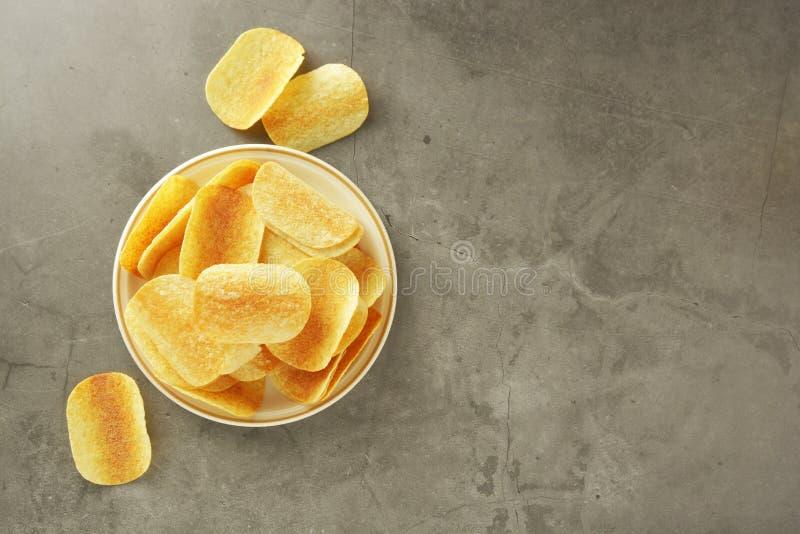 Knapperige die chips over grijze geweven achtergrond worden geïsoleerd Hoogste mening De ruimte van het exemplaar stock foto