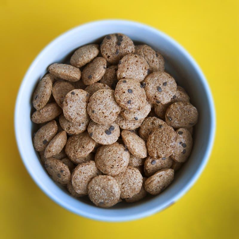 Knapperige granola isoalted Het voeden muesli met chocolade in witte ronde kom over gele achtergrond Dagelijks ontbijt Vierkante  royalty-vrije stock afbeelding