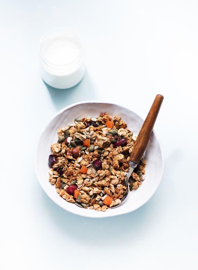 Knapperige granolamuesli met droge vruchten, noten en zaden en een kruik yoghurt stock foto