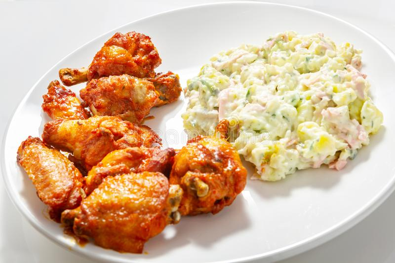 Knapperige kippenvleugels en aardappelsalade stock fotografie