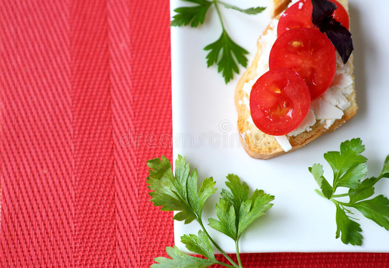 Knapperige toost met kaas en tomaat op een witte plaat stock foto