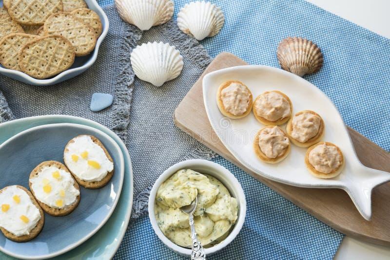 Knapperige toosts op verscheidene blauwe platen, met tonijn en zalmsalade, roomkaas en boter royalty-vrije stock afbeelding