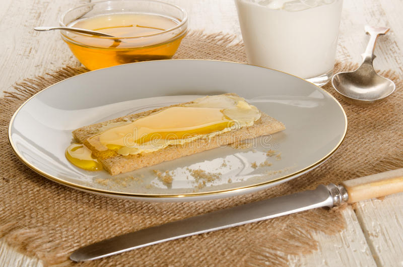 Knaprigt bröd med söt honung på en platta royaltyfri fotografi