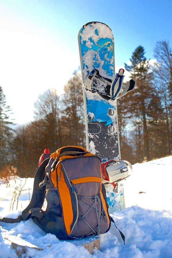 Knapsack near the snowboard. Knapsack on the snow near the snowboard stock image
