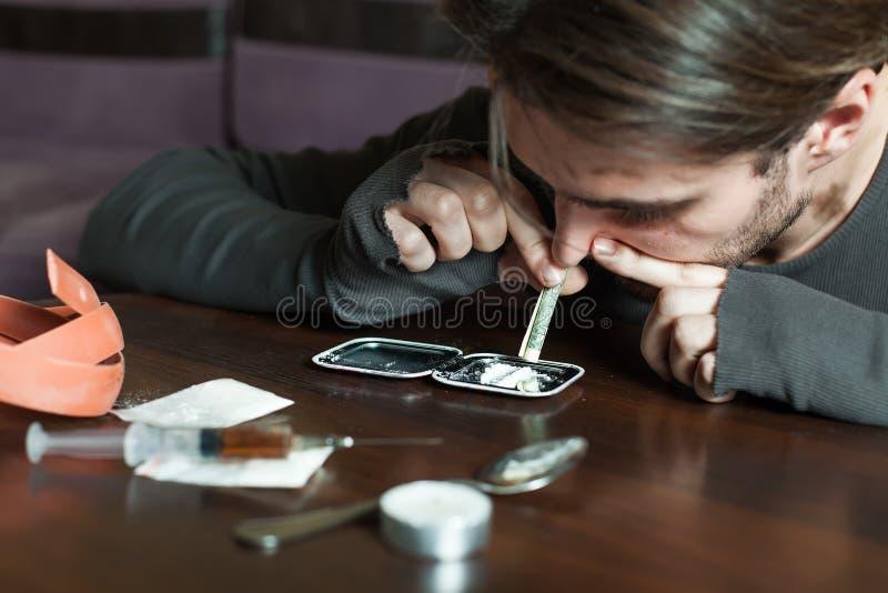Knarkaremannen luktar kokain från en spegel royaltyfri fotografi
