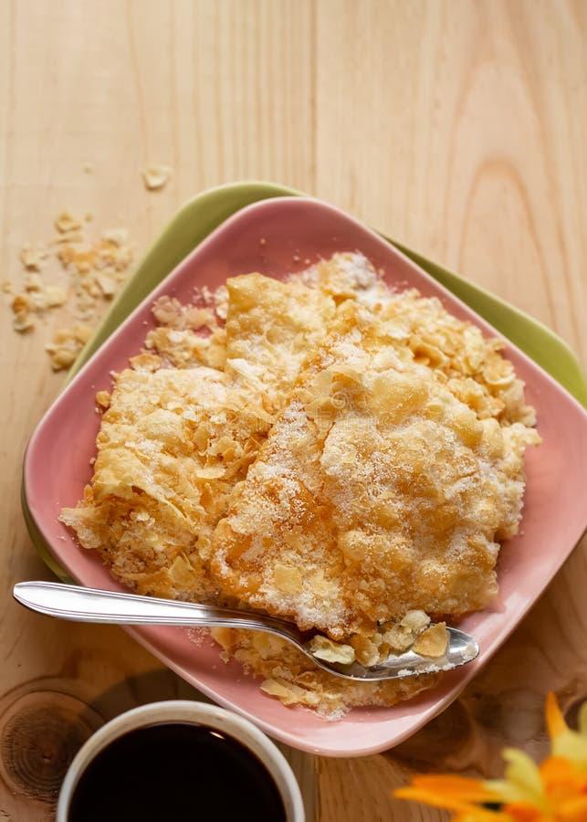 Knastrade frasiga kakor med socker p? en platta och en kopp kaffe p? en tr?tabell kopiera avst?nd royaltyfri fotografi