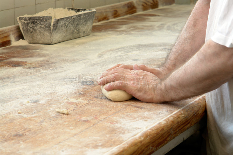 Kneading bread in baker's hand. Bread dough being kneaded by baker's hands on flour-covered wooden counter royalty free stock photos