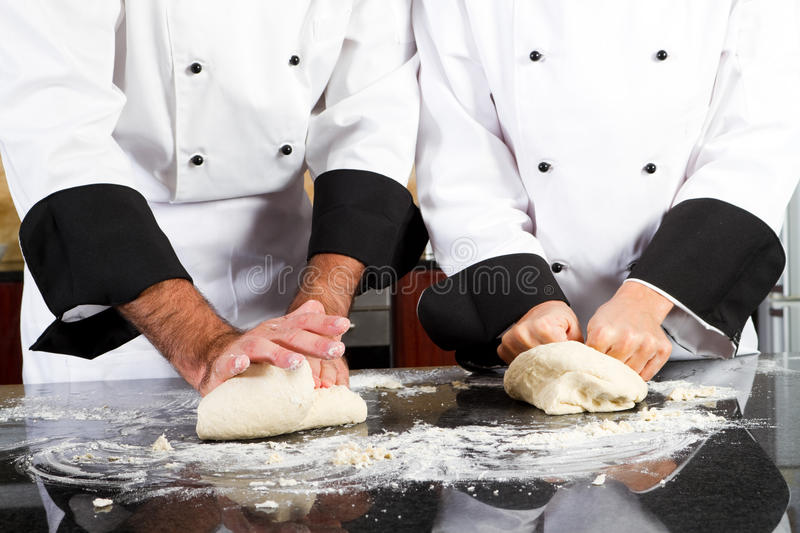 Kneading bread dough. Professional chef hands kneading bread dough on kitchen counter royalty free stock photo