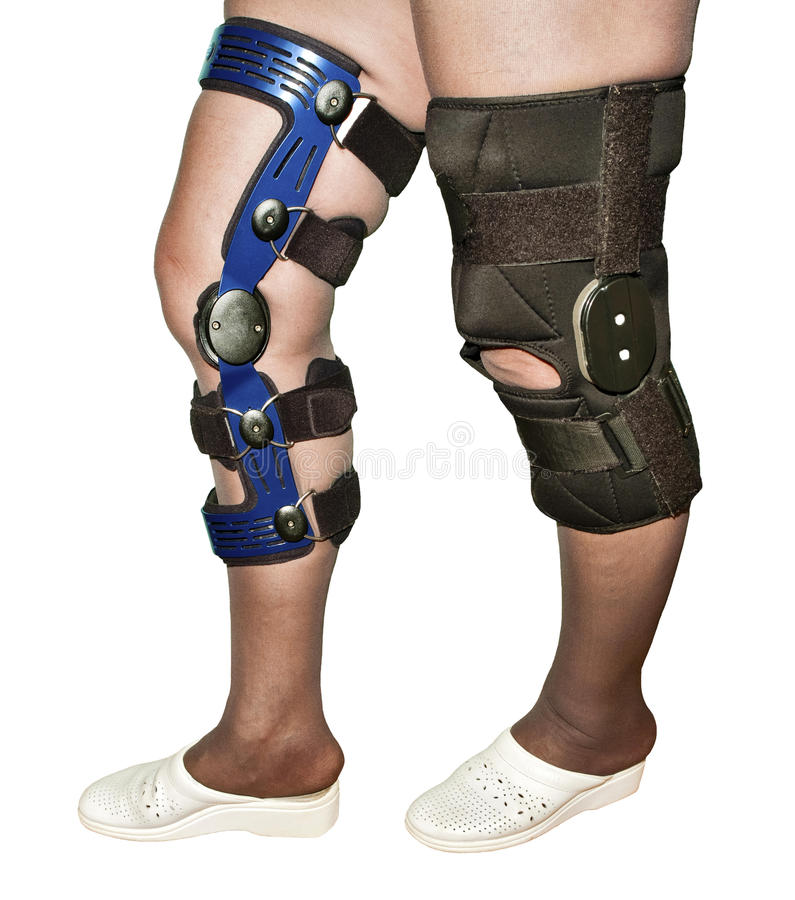 Knee braces. Female's legs in two different types of knee braces used after knees injuries isolated on white stock photos