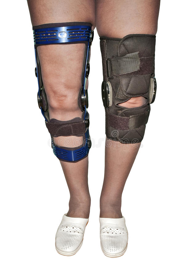 Knee braces. Female's legs in two different types of knee braces used after knees injuries isolated on white royalty free stock images
