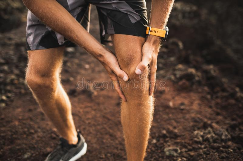 Knee injury on running outdoors. Man holding knee. By hands close-up and suffering with pain. Sprain ligament or meniscus problem royalty free stock images