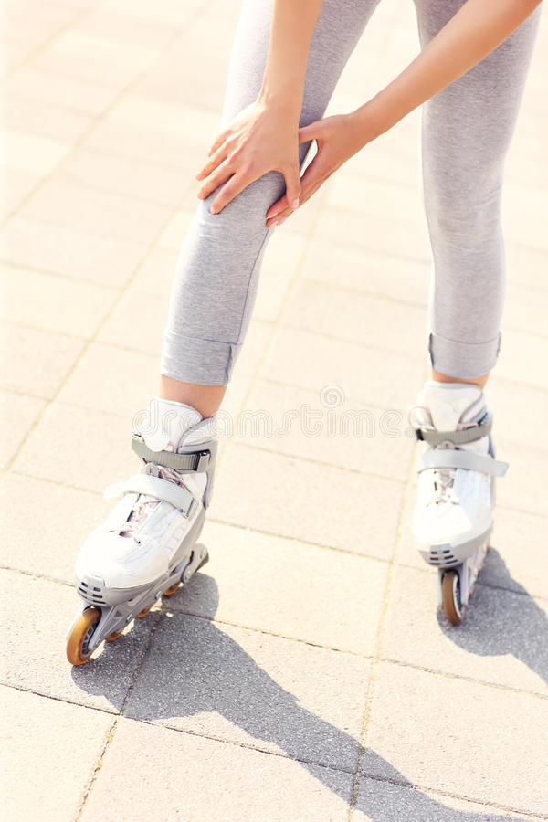 Knee pain while roller blading. A picture of a woman having problem with knee while roller blading stock image