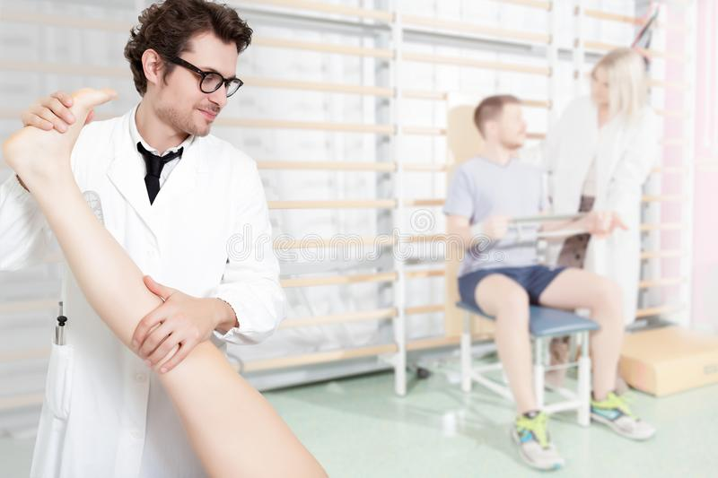 Knee rehabilitation in physiotherapy clinic. Doctor checks the leg and knee of a patient in a rehabilitation gym, on the background, a patient checked by a royalty free stock photo