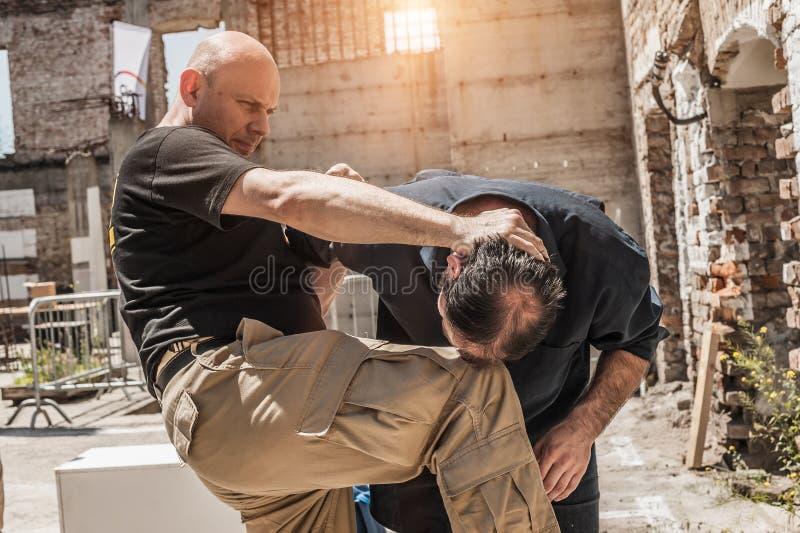 Knee strike to the head street fight stock image