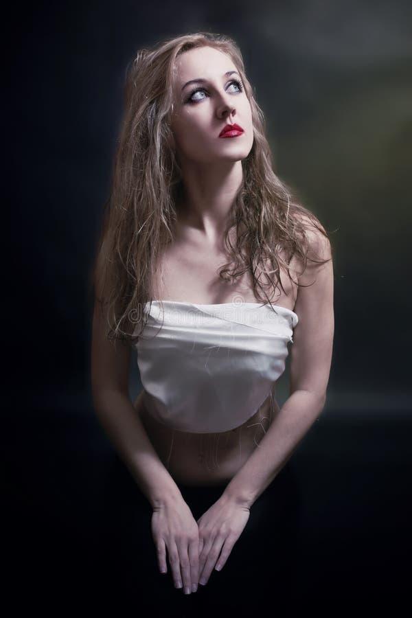 Kneelin de rogación de la mujer joven fotos de archivo libres de regalías