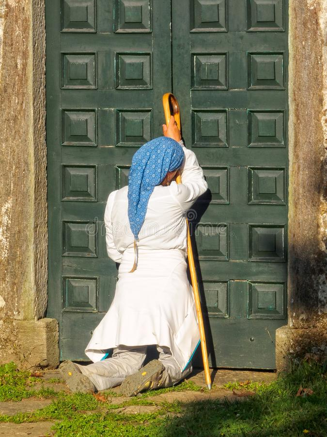 Kneeling devotee - Santa Irene. Kneeling devotee in front of the chapel door - Santa Irene, Galicia, Spain, 2 October 2014 stock photos