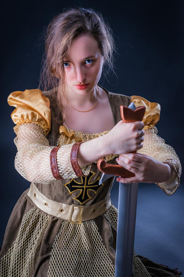 Kneeling girl princess with clear blue eyes holding a sword. Mysterious background stock images