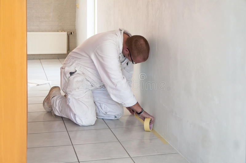 Kneeling home decorator busy with taping floor tiles royalty free stock photo