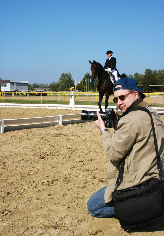 Kneeling Photographer Turned Head, Shoots Outdoor Equestrian Dressage English Riding Sports Competition, Horsewoman Jokey on Horse stock photos
