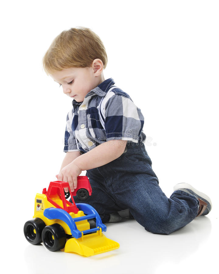 Kneeling Todler. An adorable little boy playing with a front loader on the floor. On a white background royalty free stock image