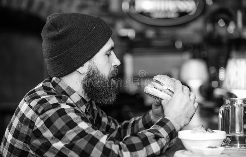 Kneipe entspannt sich Platz, um Getr?nk zu haben und sich zu entspannen Mann mit Bartgetr?nkbier essen Burgermen? Genie?en Sie Ma lizenzfreies stockbild