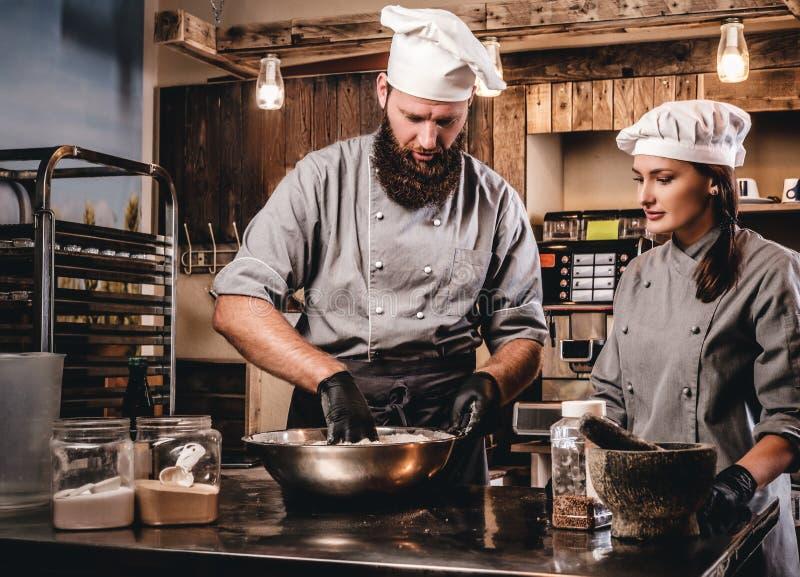 Knetender Teig des Chefs in der Küche Chef, der seinen Assistenten unterrichtet, das Brot in der Bäckerei zu backen lizenzfreie stockfotografie