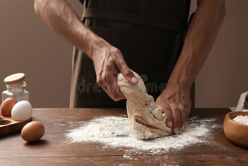 Knetender Teig des Mannes auf Holztisch stockbild