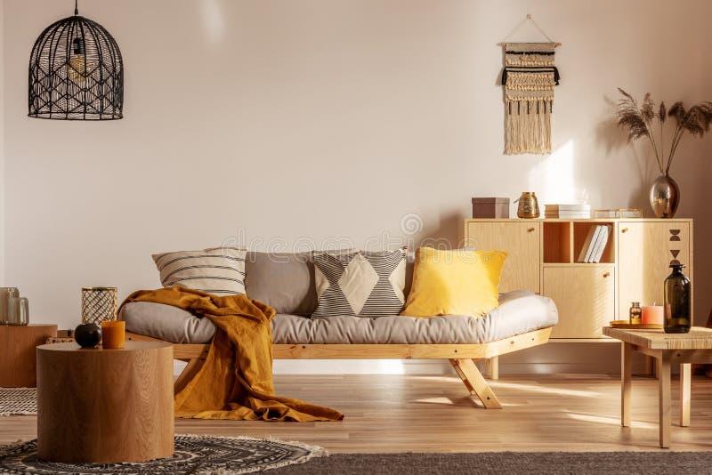 Knick knacks na drewnianym komanie za szarą kanapą z poduszkami i kocem fotografia stock