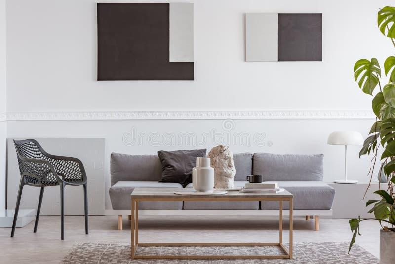 Knick knepar på den eleganta kaffetabellen framme av den gråa soffan i lyxig vardagsruminre arkivbild