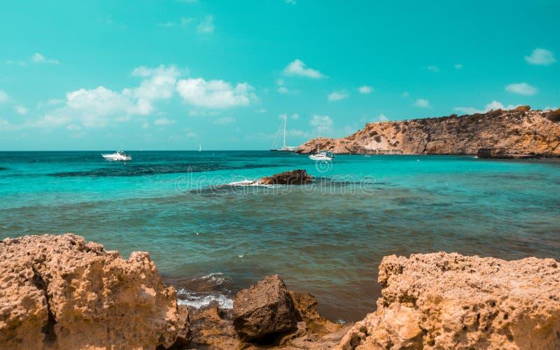 Knickente und orange Stimmung von Cala Tarida setzen mit Steinfelsen, Ibiza-Insel auf den Strand spanien lizenzfreie stockfotografie