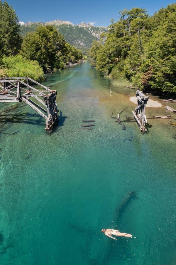 Knickentengreen river Wasser im Patagonia, Argentinien mit alter Brücken- und Mädchenschwimmen stockfoto