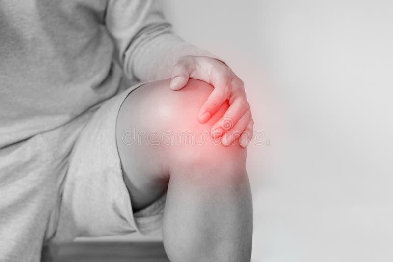 Knie gezamenlijke pijn, een mens die aan kniepijn lijden, op witte achtergrond stock foto's