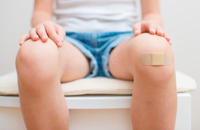 Knie mit klebendem Verband stockfotos