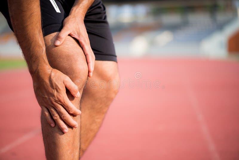 Knie-Verletzungen junger Sportmann mit den starken athletischen Beinen lizenzfreie stockfotos