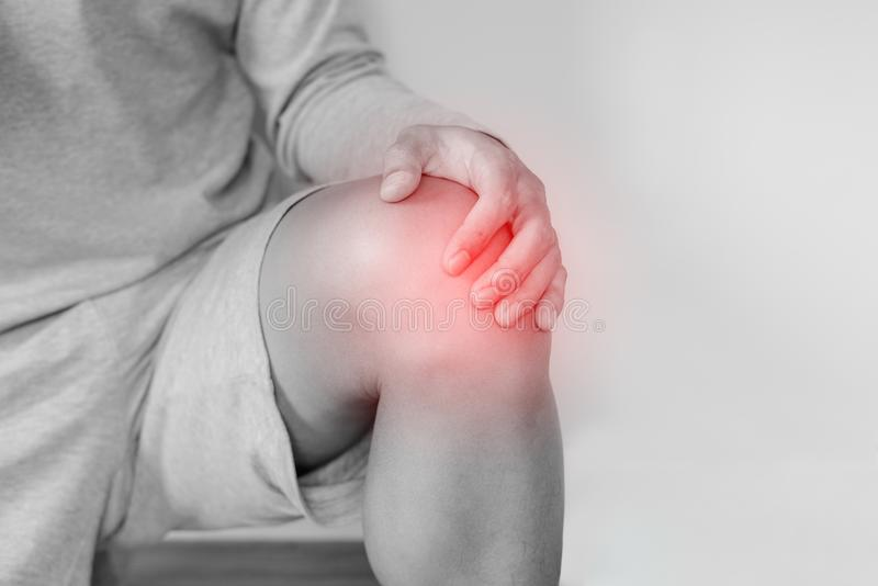 Kniegelenkschmerz, ein Mann, der unter den Knieschmerz, auf weißem Hintergrund leidet stockfotos