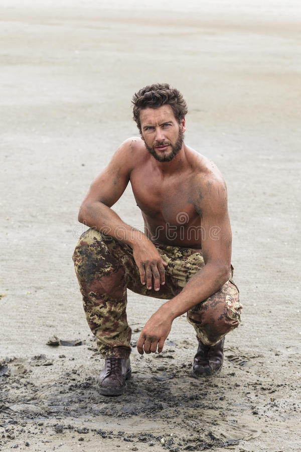 Knielende Shirtless Militair op het Strandzand stock afbeelding