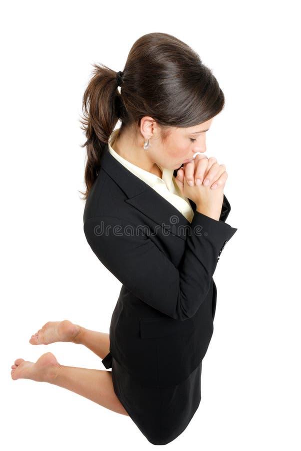 Kniende und betende Geschäftsfrau lizenzfreie stockfotos