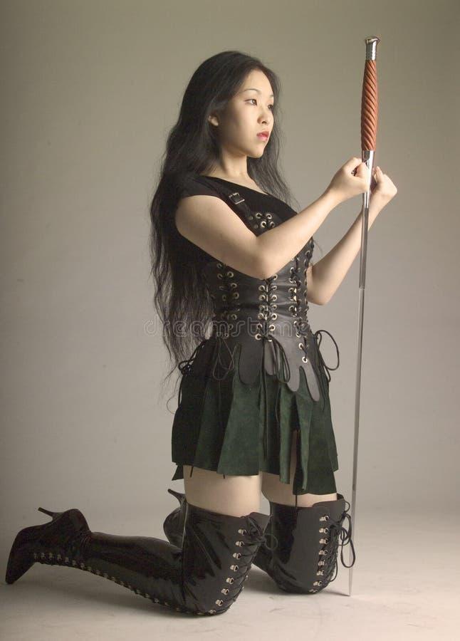 Kniender Asiatischer Krieger Mit Klinge Stockfoto