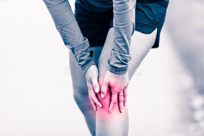 Kniepijn, vrouw die pijnlijk en pijnlijk been houden stock afbeelding