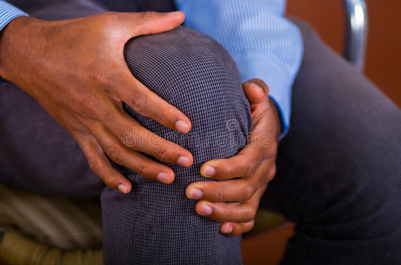 Knieschmerz auf einem Mann, beide Hände, die ihn halten und irgendeine Massage machen stockbild