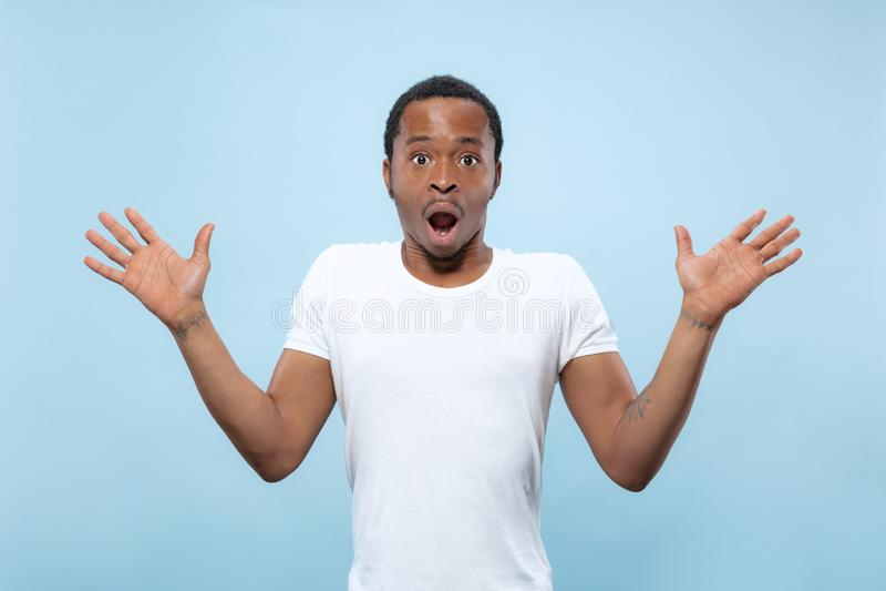 Kniestückabschluß herauf Porträt des jungen Mannes auf blauem Hintergrund lizenzfreies stockfoto
