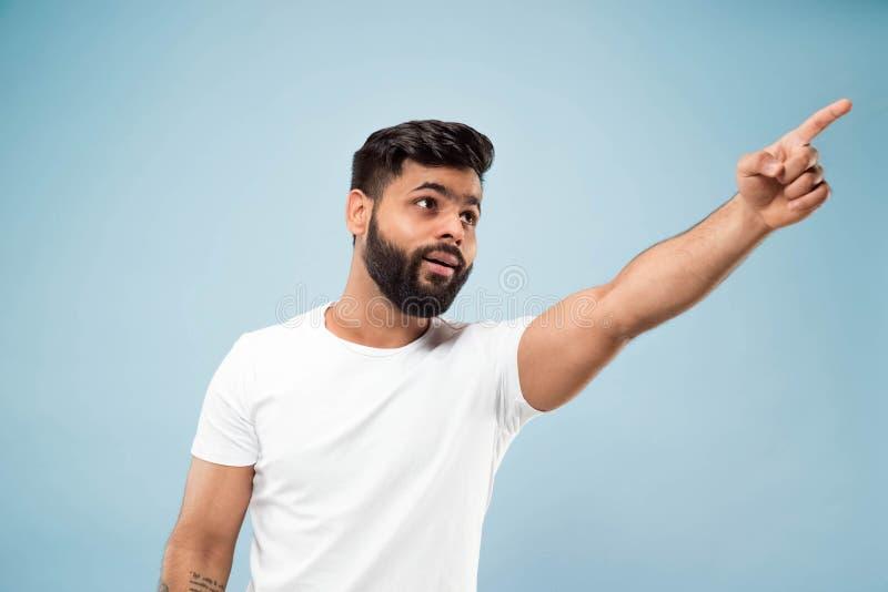 Kniestückabschluß herauf Porträt des jungen Mannes auf blauem Hintergrund stockbild
