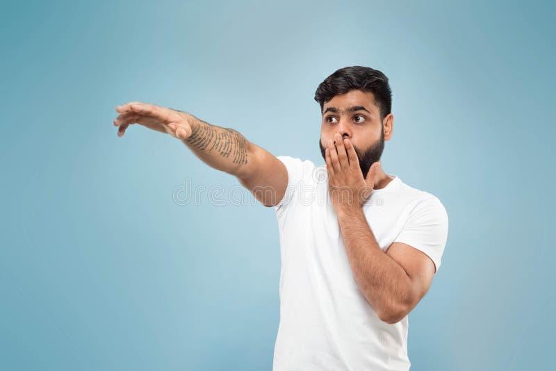 Kniestückabschluß herauf Porträt des jungen Mannes auf blauem Hintergrund stockfoto