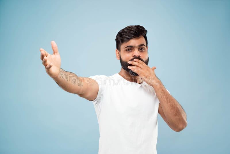 Kniestückabschluß herauf Porträt des jungen Mannes auf blauem Hintergrund stockfotos
