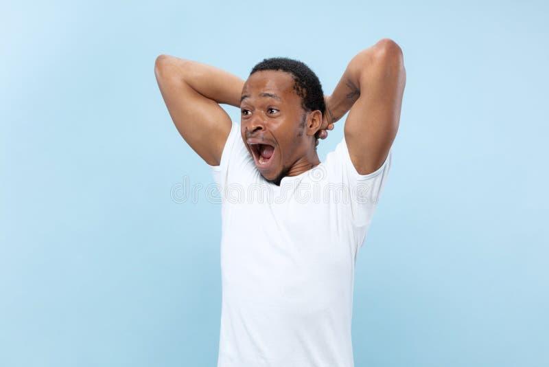 Kniestückabschluß herauf Porträt des jungen Mannes auf blauem Hintergrund stockbilder