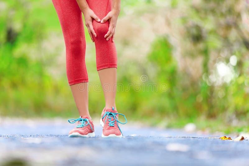 Knieverwonding - sporten die knieverwondingen op vrouw in werking stellen stock foto's