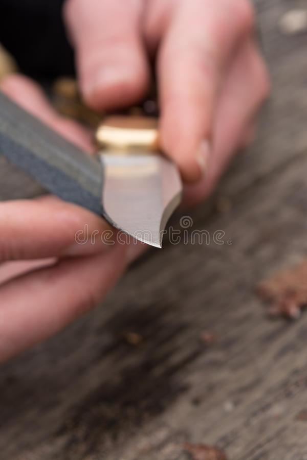 Knife being sharpened. Male hands sharpening large pocket knife with a wetstone royalty free stock images