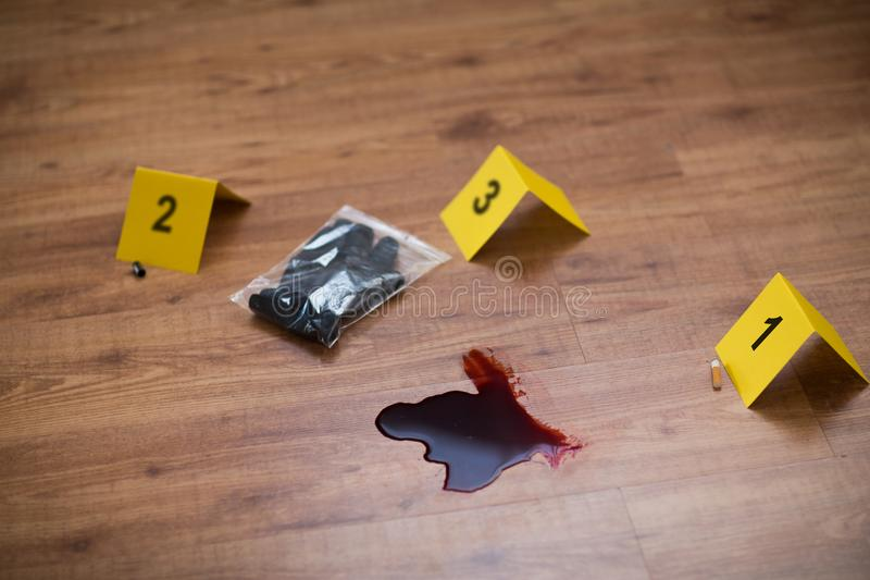 Knife in blood and evidence marker at crime scene stock photos