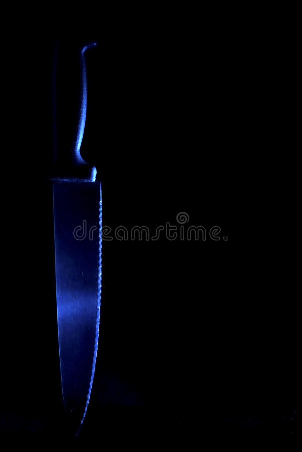 Knife in cold light. A knife photographed in cold, blue light.The blue light gives this image its creepy appearance stock photography
